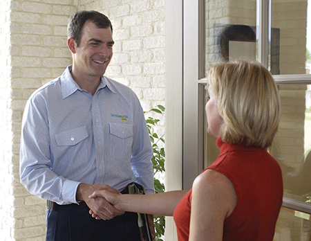 technician shaking hands with woman