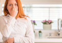 woman holding her nose from bad odor