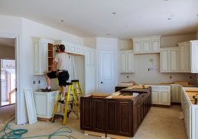 construction worker installing kitchen cabinets
